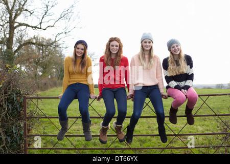 Four teenage girls sitting on gate - Stock Photo