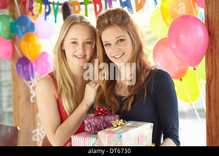 Two teenage girls sharing gifts at birthday party - Stock Photo