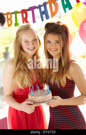 Two teenage girls holding birthday cake - Stock Photo