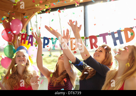 Four teenage girls celebrating with confetti at birthday party - Stock Photo