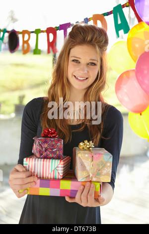 Portrait of teenage girl holding birthday gifts - Stock Photo
