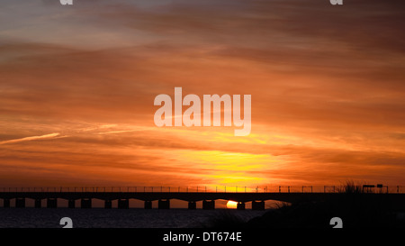 orange glowing dramatic sunrise over the Great Belt Bridge, crossing the Baltic Sea, in spring - Stock Photo