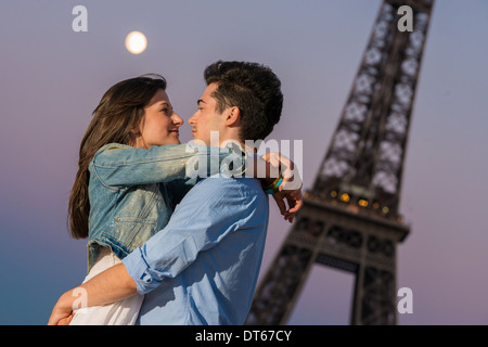 Young couple embracing in moonlight, Paris, France - Stock Photo