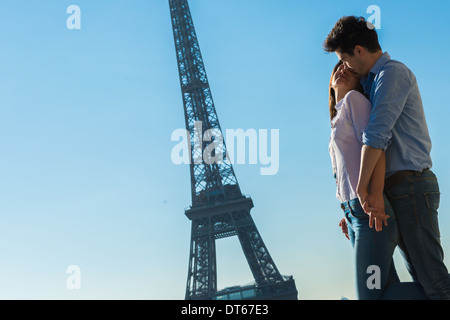 Young couple embracing near Eiffel Tower, Paris, France - Stock Photo