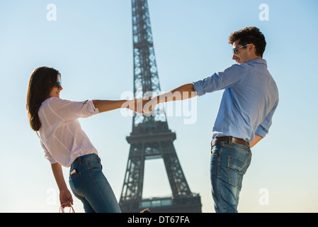 Young couple in front of Eiffel Tower, Paris, France - Stock Photo