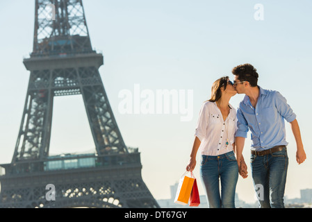 Young couple kissing near Eiffel Tower, Paris, France - Stock Photo
