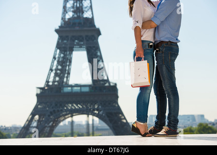 Young couple embracing in front of Eiffel Tower, Paris, France - Stock Photo