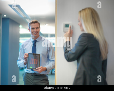 Office workers adjusting heating thermostat and recording information on digital tablet - Stock Photo