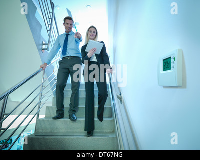 View of thermostat in office stairwell with workers walking down stairs - Stock Photo