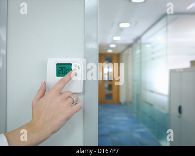 Close up of office worker adjusting thermostat - Stock Photo