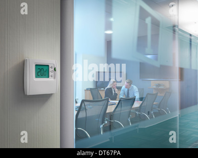 Thermostat outside conference room with office workers in meeting - Stock Photo