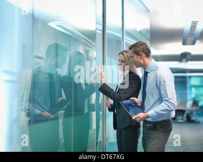 Office workers adjusting heating thermostat in modern workplace - Stock Photo