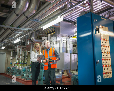 Office workers using digital tablet and camera to check efficiency of office heating in boiler room - Stock Photo