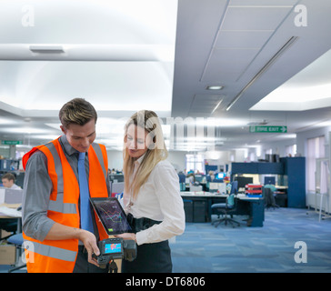 Office workers looking at digital tablet and thermal infrared images in office - Stock Photo