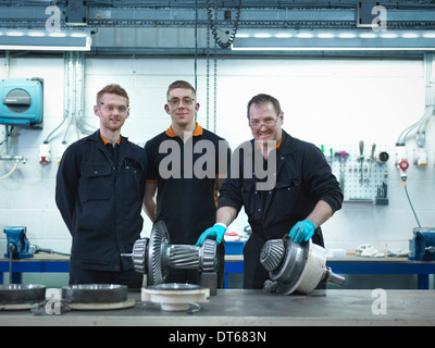 Engineer teaching apprentices in engineering factory, portrait - Stock Photo
