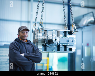 Engineer with industrial gearbox in engineering factory, portrait - Stock Photo