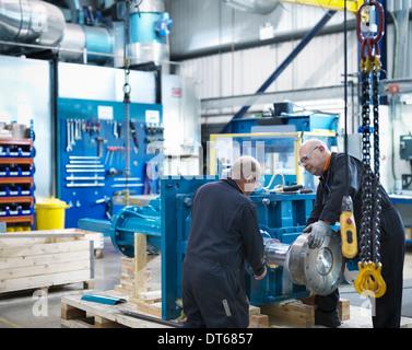 Mature engineers working in engineering factory - Stock Photo