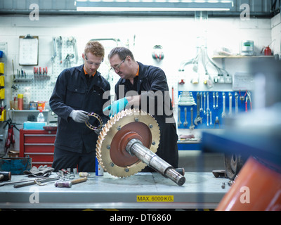Engineer teaching apprentice in engineering factory - Stock Photo