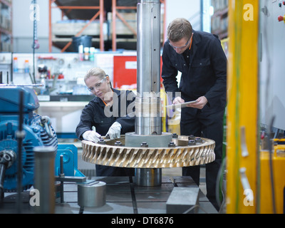 Engineers assembling industrial gearbox in engineering factory - Stock Photo