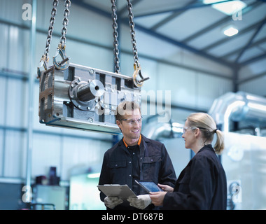 Engineers discuss plans on digital tablet in engineering factory - Stock Photo