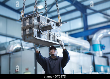 Engineer using crane to move industrial gearbox to paint works in engineering factory - Stock Photo