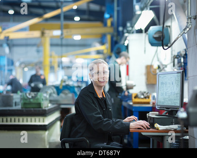 Female engineer using computer in engineering factory, portrait - Stock Photo