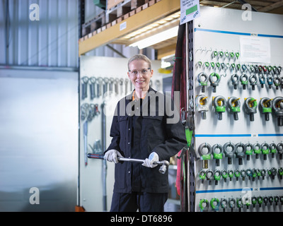 Female worker in engineering factory holding lifting gear, portrait - Stock Photo