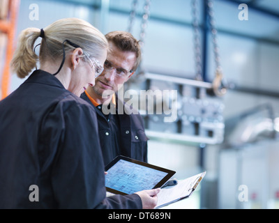 Engineers inspect plans on digital tablet in engineering factory - Stock Photo