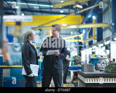 Workers in discussion in engineering factory - Stock Photo