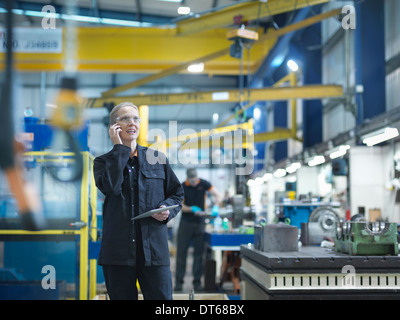 Female worker using mobile phone in engineering factory - Stock Photo