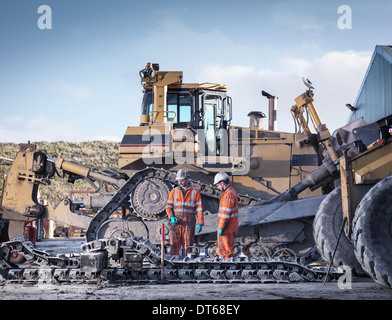 Apprentice and engineer work on machinery in surface coal mine - Stock Photo