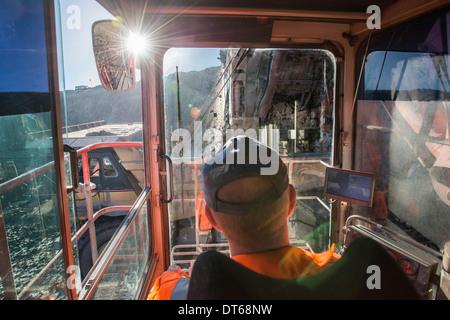 Excavator driver in digger cab at surface coal mine - Stock Photo