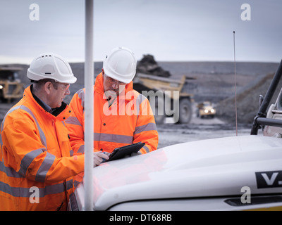 Geologists discuss plans on digital tablet in surface coal mine - Stock Photo