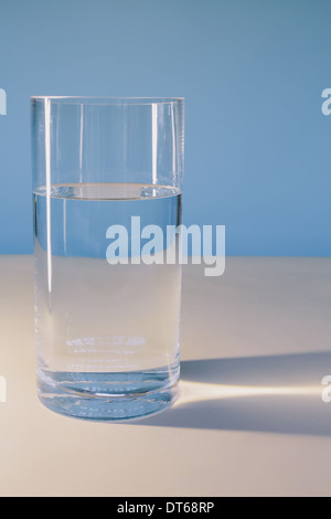 A glass of filtered water on a white surface. - Stock Photo