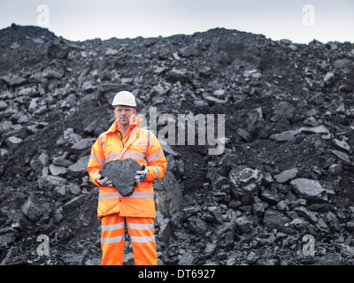 Portrait of coal miner holding coal in surface coal mine - Stock Photo