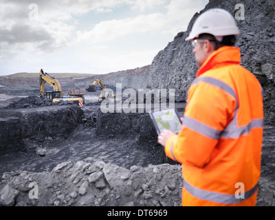 Miner checks plans on digital tablet in surface coal mine - Stock Photo
