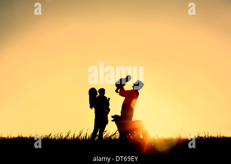 A silhouette of a happy family of four people, mother, father, baby, and child, and their dog in front of a sunsetting - Stock Photo