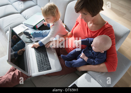 Mother, baby boy and female toddler using laptop on sofa - Stock Photo