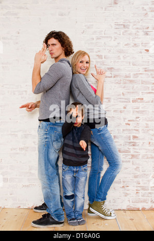Studio portrait of couple and son making gun hand gestures - Stock Photo