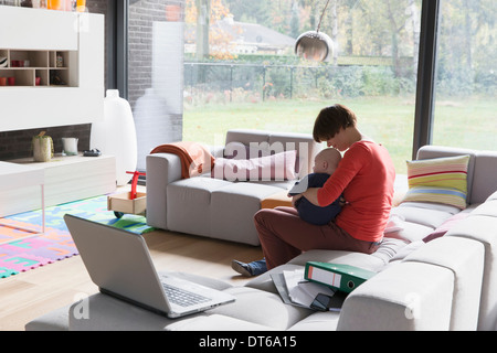 Mother with baby boy sitting on sofa at home - Stock Photo