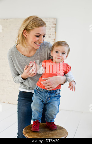 Studio portrait of mother holding baby daughter - Stock Photo