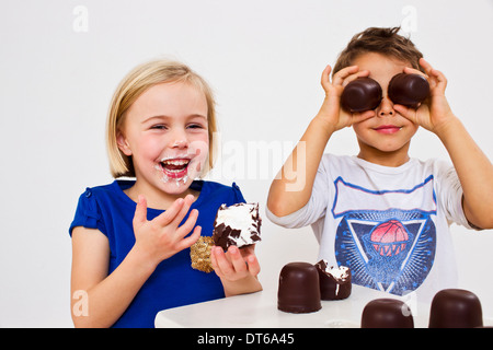 Studio shot of brother and sister with chocolate marshmallows - Stock Photo