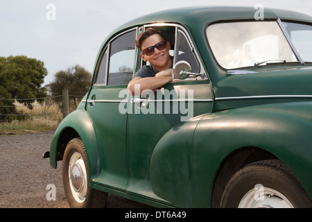 Portrait of young man in vintage morris minor - Stock Photo