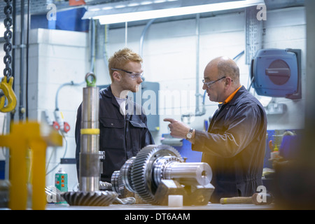 Engineer instructing apprentice at workstation in factory - Stock Photo