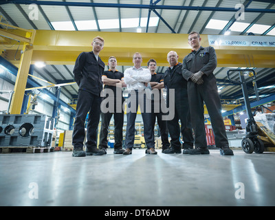 Group of engineers and apprentices in engineering factory, portrait - Stock Photo