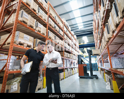 Workers using digital tablet in parts store in factory - Stock Photo