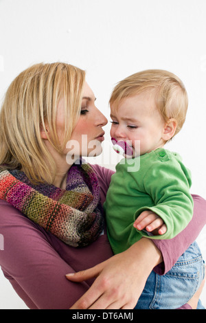 Studio portrait of mother trying to soothe baby daughter - Stock Photo