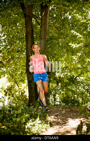 Young woman running in woods - Stock Photo