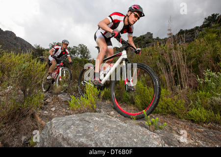 Young couple riding mountain bikes on dirt track - Stock Photo