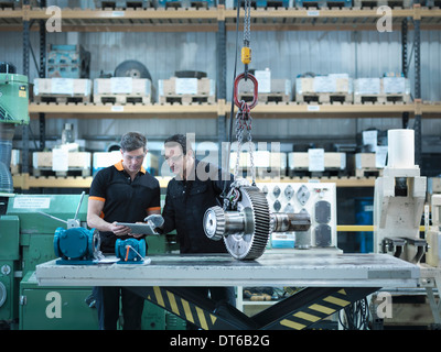 Engineers using digital tablet with gear wheel at work station - Stock Photo